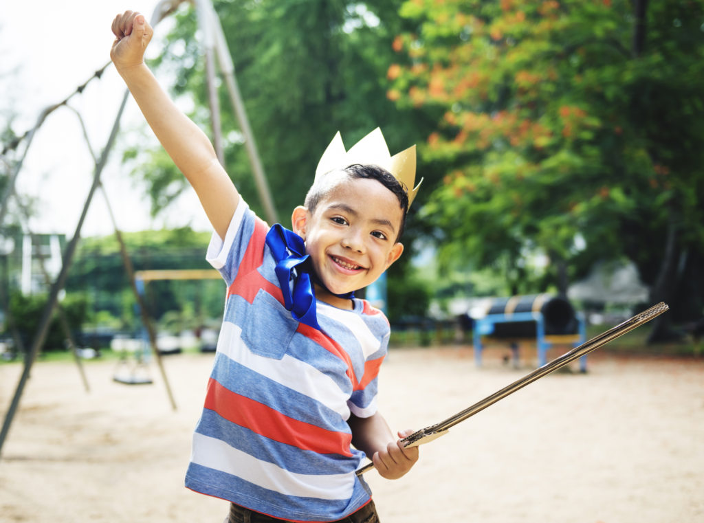 Excited preschool boy on playground wearing crown with cardboard sword