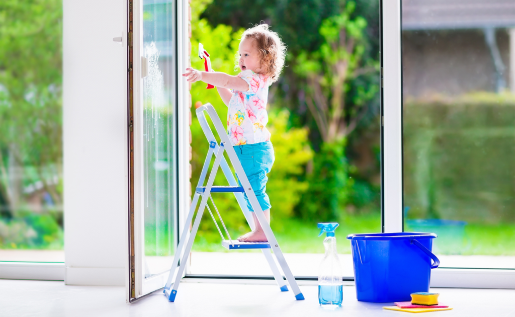 Little girl on step ladder cleaning windows