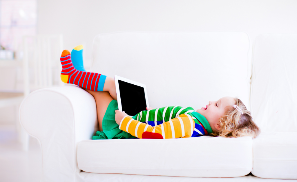Child laying on couch with ipad in her lap